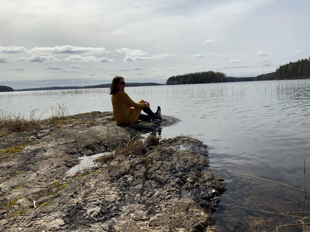 nainen istuu rantakivellä ja katsoo järvelle