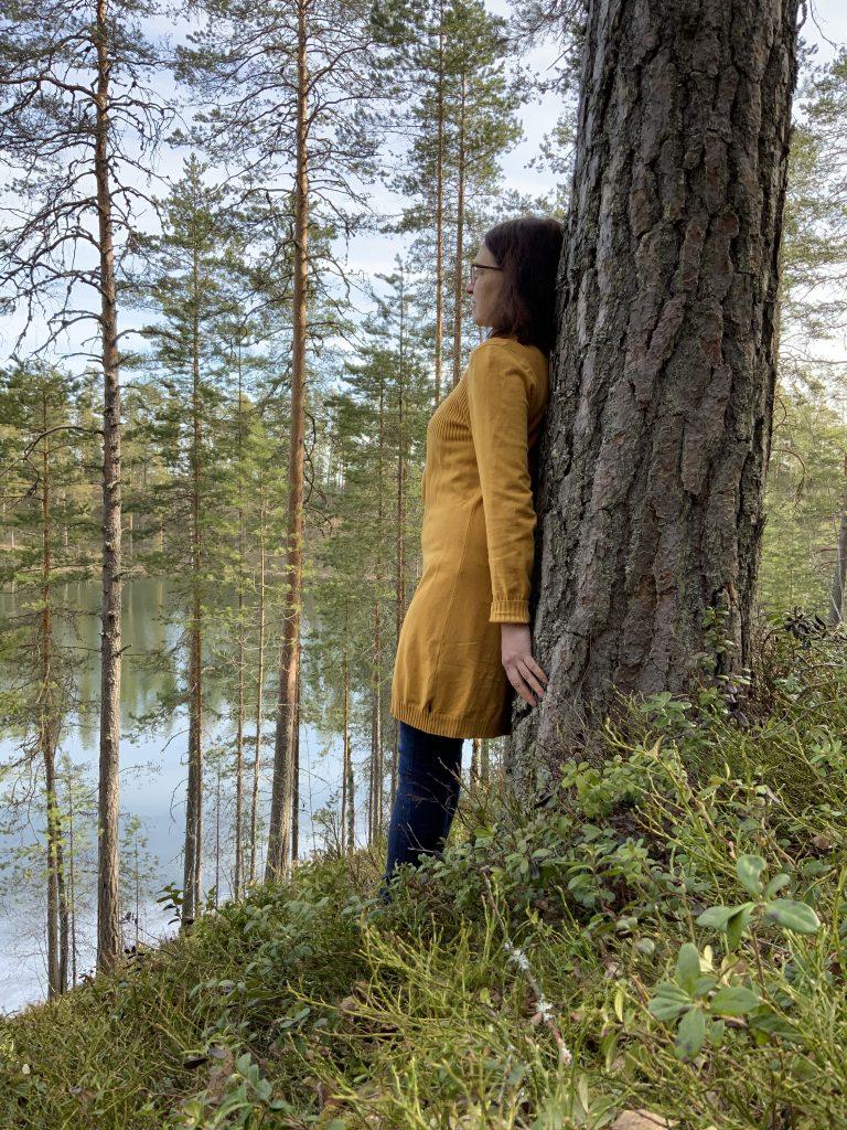 nainen nojaa mäntyyn ja katselee järvelle